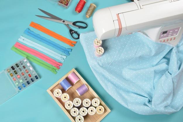 Vlakke lay van naaimateriaal bevat de stoffen, schaar, rits, pin en draad rollen.
