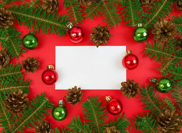 Vlakke leggen met blanco papier met spar boomtakken, kegels en kerstballen op rood