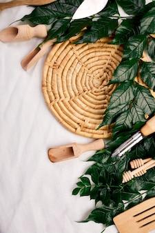 Vlakke leggen met houten keukengerei met groene bladeren, kookgerei