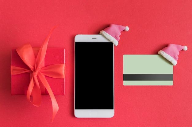 Vlakke leggen met kerstcadeau doos, smartphone en creditcard met kerstmuts op rood