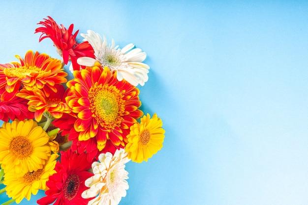 Vlakke leggen met kleurrijke rood geeloranje herfstbloemen op lichtblauw gekleurde achtergrond. bright fall, thanksgiving day concept. bovenaanzicht, kopieer ruimte
