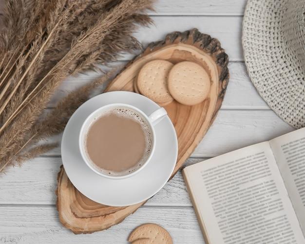 Vlakke leggen met kopje espresso op houten plakje met koekjes en boek. bovenaanzicht.