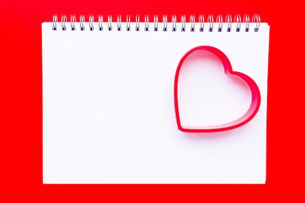 Vlakke leggen met lege witte notebook en rood hart op rood