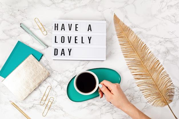 Vlakke leggen met lightbox met tekst have a lovely day and coffee cup in woman hand. sociale media, motivatiecitaat, vrouwelijke blog, ochtend van werkdagconcept