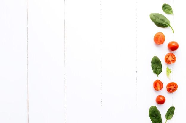 Vlakke leggen met rode kerstomaatjes en groene spinazieblaadjes op een witte houten achtergrond. gezond eten concept