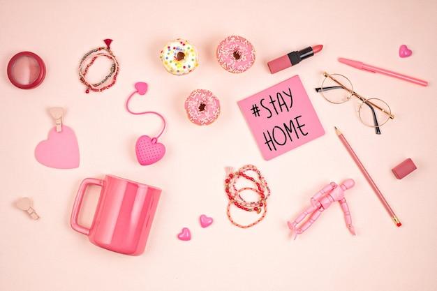 Vlakke leggen met roze accessoires, theekop en donuts over lichtroze muur. bovenaanzicht. ochtendrituelen, blijf thuis concept