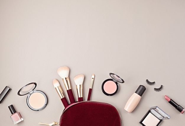 Vlakke leggen met set van professionele decoratieve cosmetica, make-up tools en vrouw accessoires over grijze muur met kopie ruimte. beauty blog, mode, party en shopping concept. bovenaanzicht