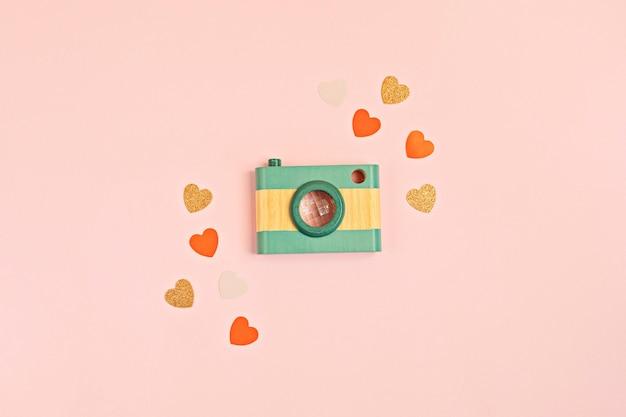 Vlakke leggen met speelgoed houten camera en harten over roze muur. social media, posts, likes, volgers, online fotografie klassen concept. bovenaanzicht, kopieer ruimte.