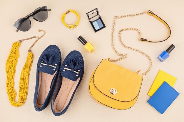 Vlakke leggen met vrouw modeaccessoires in gele en blauwe kleuren. modeblog, zomerstijl, winkelen en trendsconcept