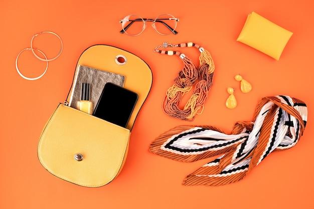 Vlakke leggen met vrouw modeaccessoires in gele kleur over oranje lederen getextureerde muur. mode, online beautyblog, zomerstijl, winkelen en trendsconcept