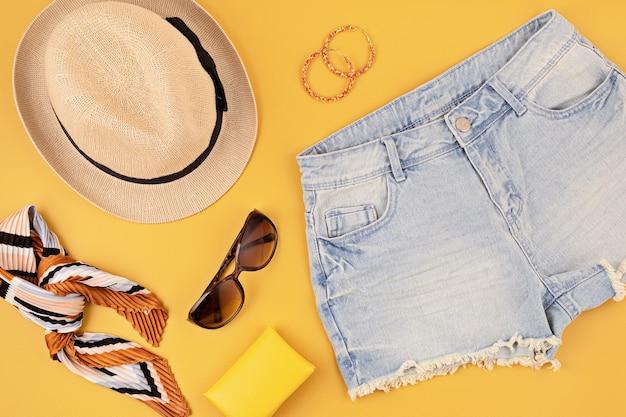 Vlakke leggen met vrouw modeaccessoires, jeans broek, hoed, zonnebril over gele muur. mode, online beautyblog, zomerstijl, winkelen en trendsconcept. bovenaanzicht