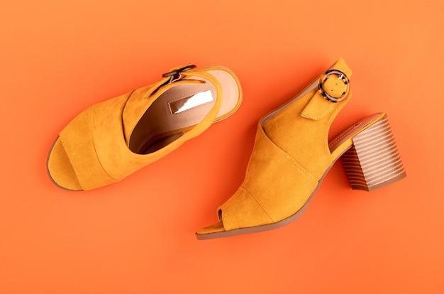 Vlakke leggen met vrouw zomer gele schoenen kleur over oranje lederen getextureerde muur. mode, online beautyblog, zomerstijl, winkelen en trendsconcept