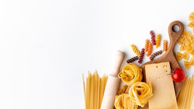Vlakke mix van ongekookte pasta en harde kaas met kopie ruimte