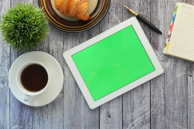 Vlakke samenstelling van digitale tablet-, thee- en kantoorleveranciers op tafel