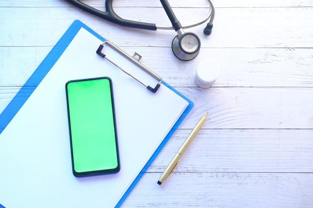 Vlakke samenstelling van slimme telefoon met leeg scherm op kliniektafel