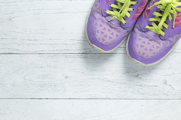 Vlakke sport lag schoenen op witte houten achtergrond met copyspace.