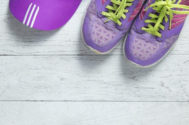 Vlakke sport leg paarse schoenen en glb op witte houten achtergrond.