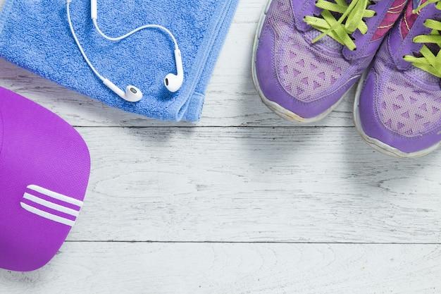 Vlakke sport leg paarse schoenen en glb op witte houten achtergrond