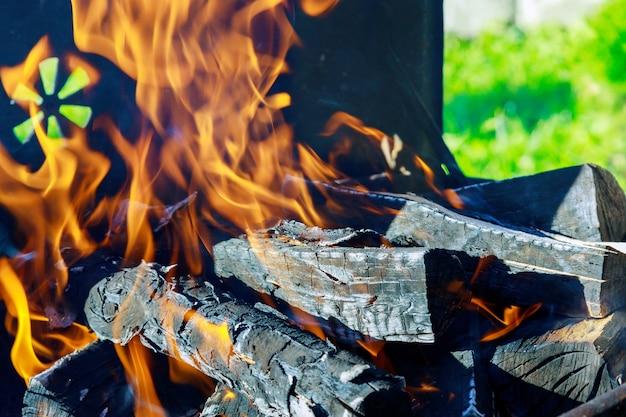 Vlammen gaan door rooster van barbecue met brandhout