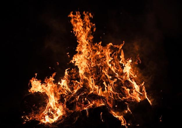 Vlammen van vreugdevuur 's nachts. brand vlammen op een zwarte achtergrond