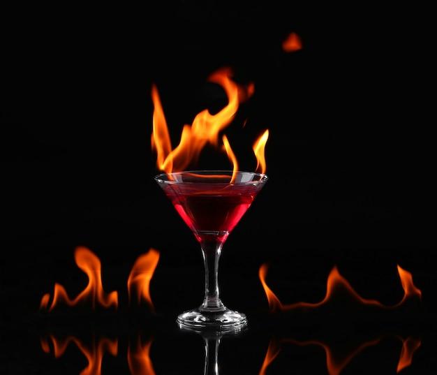 Vlammende cocktail op zwarte achtergrond