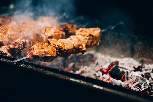 Vlees aan het spit. varkensvlees grill. roken barbecue op straat. kip sjasliek koken. kolen verbranden.