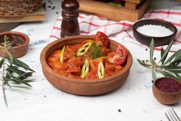 Vlees aardappel stoofpot met tomatensaus en peper in aardewerk kom.