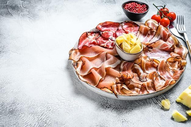 Vlees antipasto schotel, pancetta, salami, gesneden ham, worst, prosciutto, spek. grijze achtergrond. bovenaanzicht.