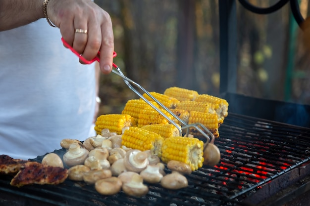 Vlees champignons maïs gegrilde maïs outdoor barbecue hand met vleestang