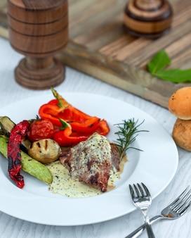 Vlees doordrenkt met saus en sesamzaadjes en groenten