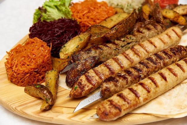 Vlees en groenten op een houten bord.