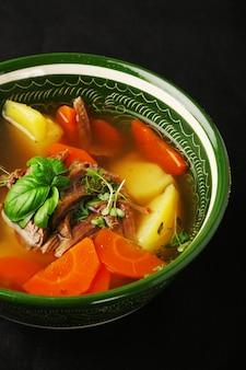 Vlees- en groentesoep met kruiden wortel en aardappel op donkere betonnen tafel close-up. shurpa soep