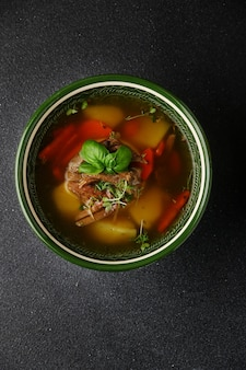 Vlees- en groentesoep met kruiden, wortel en aardappel op donkere betonnen tafelbladweergave. shurpa soep