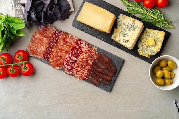 Vlees en kaas snijden op grijze achtergrond bovenaanzicht