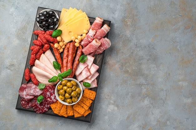 Vlees en kaas voorgerecht, olijven en basilicum op een grijze achtergrond