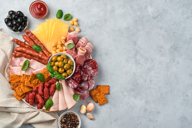 Vlees- en kaasdelicatessen met olijven, saus, kruiden en knoflook.