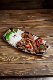 Vlees en kip kebab met rijst en gehakte uien