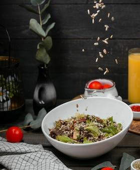 Vlees en kruidensalade gegarneerd met zonnebloempitten