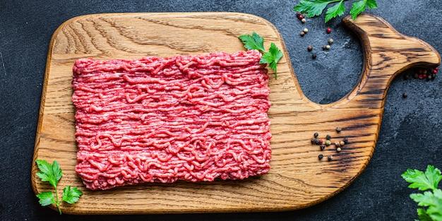 Vlees gemalen gehakt varkensvlees of rundvlees op houten tafel, bovenaanzicht