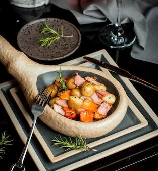 Vlees geserveerd met aardappelen, rozemarijn en paprika
