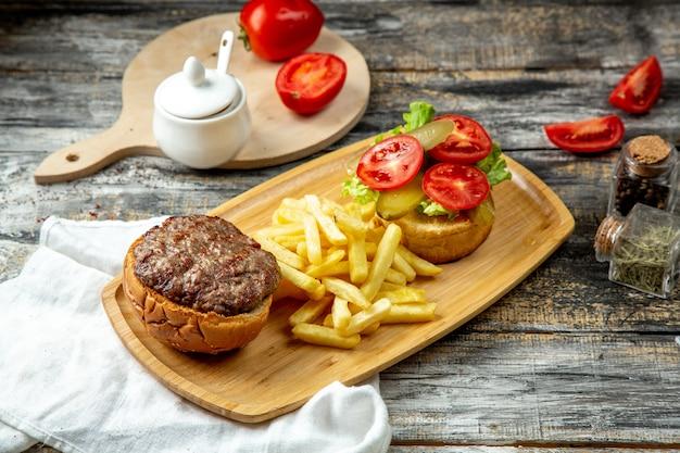Vlees hamburger tomatensla frietjes zijaanzicht