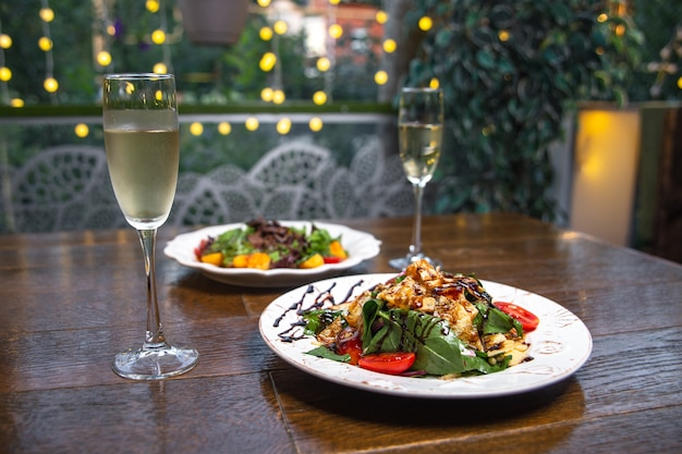 Vlees met aardappelen en champagne op een houten tafel