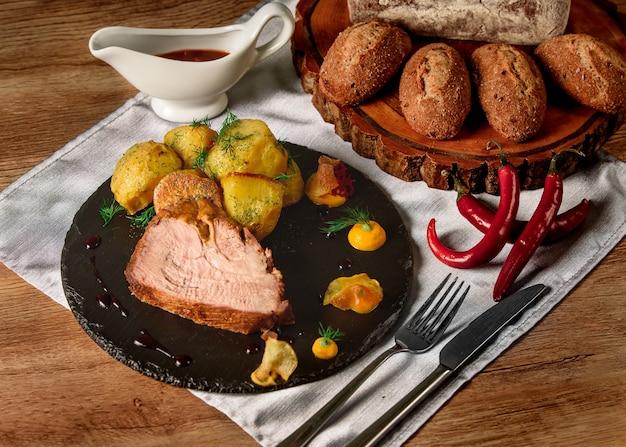 Vlees met gebakken aardappelen met dille, saus en mosterd op een zwarte leischotel naast chilipepers en broodjes en brood op een houten bord.
