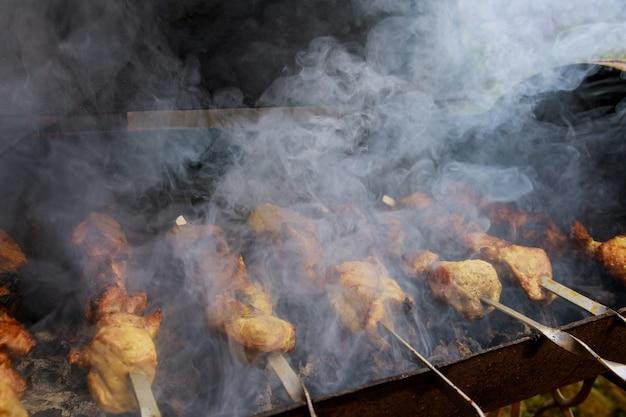 Vlees met rook aan metalen spiesjes wordt gegrild met brandende houtskool