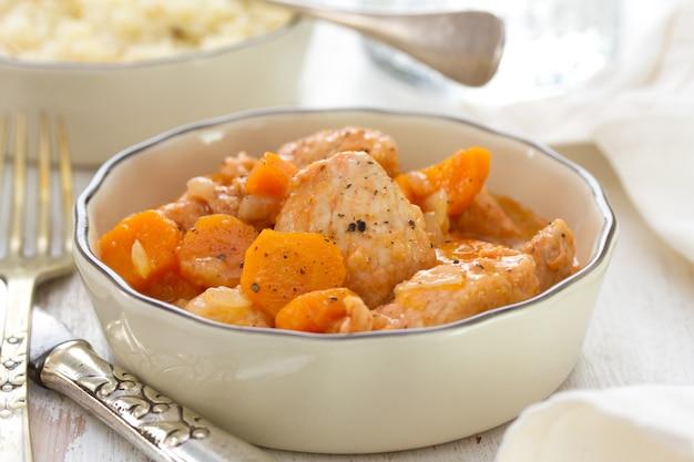 Vlees met wortel in kom met vork en mes