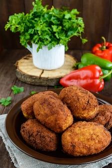 Vlees minibroodjes met gekookt ei in een kleikom op donker hout.