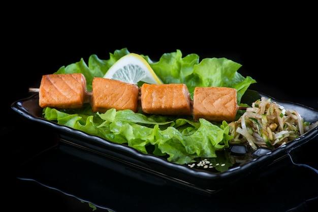 Vlees op houten spiesen, varkensvlees, kip, vis, sint-jakobsschelp, rundvlees, garnalen in een zwarte plaat op een zwarte muur.