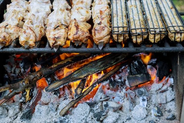 Vlees op metalen spiesjes wordt gegrild met brandende houtskool.