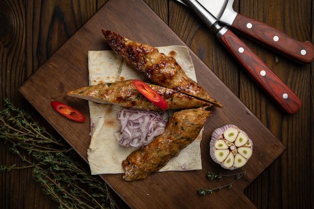 Vlees op pitabroodje met knoflook op een houten tafel