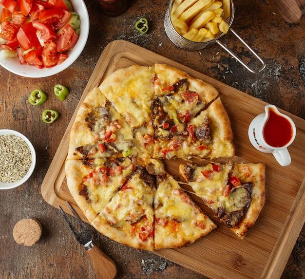 Vlees pizza met frietjes bovenaanzicht